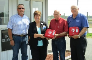 Theresa Rutherford (second from left), HSHS St. Anthony's Memorial Hospital President and CEO, presents one of two Automated External Defibrillators (AEDs), to members of the Effingham County Fair Board.  With Rutherford are (left to right) Dale Laue, Wilbert Schaefer, and Phil Hartke. HSHS St. Anthony's donated two AEDs to the fairgrounds and will also be providing Heartsaver AED CPR training for 15-20 staff and volunteers connected with the fairgrounds.